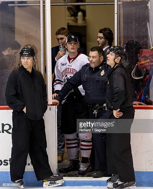 Adam Gaudette of the Northeastern Huskies looks from the tunnel after a Zamboni ice resurfacer was towed off the ice after it broke down between the...