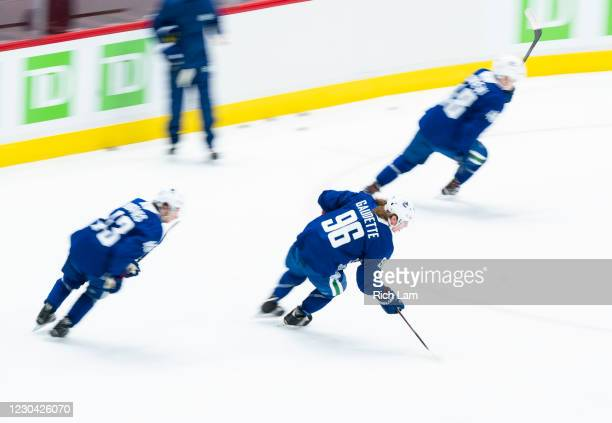 Adam Gaudette of the Vancouver Canucks along with Quinn Hughes and Olli Juolevi skate on the first day of the Vancouver Canucks NHL Training Camp on...