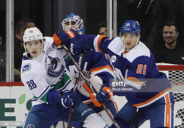 Adam Gaudette of the Vancouver Canucks and Luca Sbisa of the New York Islanders battle for position in the crease during the second period at the...