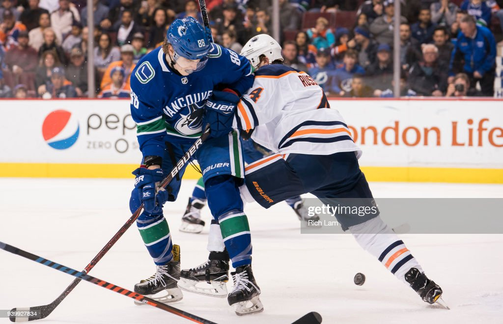 Adam Gaudette #88 of the Vancouver Canucks battles for the puck against Kris Russell #4 of the Edmonton Oilers against the Edmonton Oilers in NHL action on March, 29, 2018 at Rogers Arena in Vancouver, British Columbia, Canada. This is Gaudette's first NHL game.