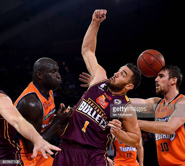 Adam Gibson of the Bullets contests the ball with Nathan Jawai and Mitch McCarron of the Taipans during the round six NBL match between the Cairns...