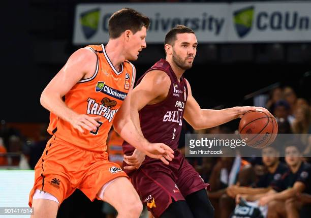 Adam Gibson of the Bullets looks to get past Cam Gliddon of the Taipans during the round 13 NBL match between the Cairns Taipans and the Brisbane...