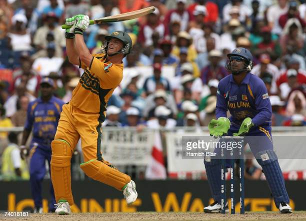 Adam Gilchrist of Australia hits a six straight down the ground with Kumar Sangakkara of Sri Lanka looking on during the ICC Cricket World Cup Final...