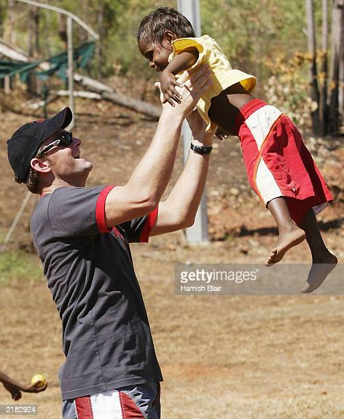 Adam Gilchrist of Australia meets a local on July 22 2003 during a team visit to an Aboriginal settlement on Melville Island off the coast of Darwin...