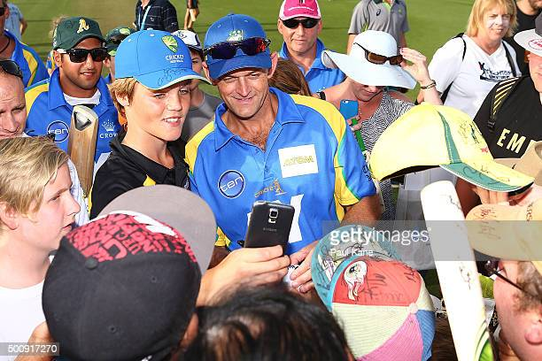 Adam Gilchrist of the Legends poses with spectators for photos following the WA Festival of Cricket Legends Match between the Australian Legends XI...