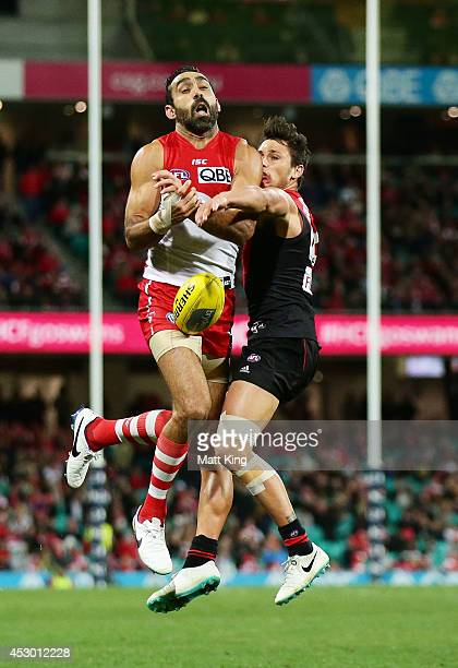 Adam Goodes of the Swans is challenged by Mark Baguley of the Bombers during the round 19 AFL match between the Sydney Swans and the Essendon Bombers...