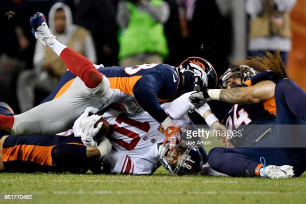 Adam Gotsis of the Denver Broncos Von Miller and Domata Peko sack Eli Manning of the New York Giants during the second quarter of the on Sunday...