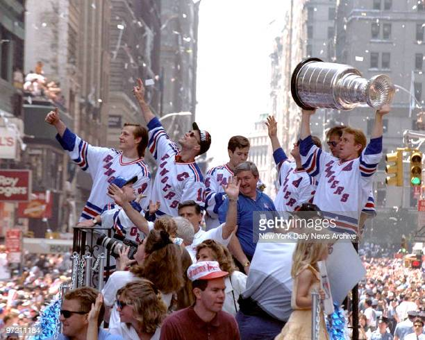 Adam Graves and Captain Mark Messier with Ranger teammates' ride through the Canyon of Heroes raising the Stanley Cup aloft are swept up in a swirl...
