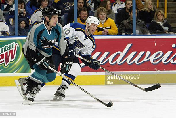 Adam Graves of the San Jose Sharks and Dallas Drake of the St Louis Blues race to the puck during the game on February 8 2003 at the Savvis Center in...