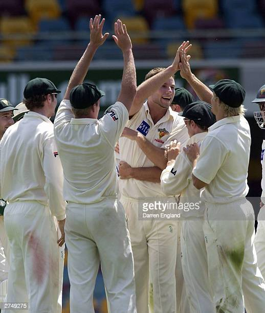 Adam Griffith of Tasmania and team mates celebrate the wicket of Wade Seccombe of Queensland during the Pura Cup match between the Queensland Bulls...