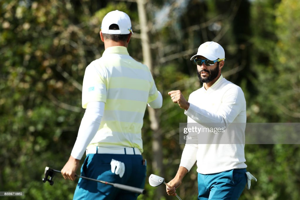 Adam Hadwin of Canada and the International Team and Adam Scott of Australia and the International Team react on the 13th green during Saturday foursome matches of the Presidents Cup at Liberty National Golf Club on September 30, 2017 in Jersey City, New Jersey.