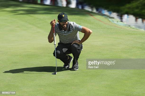 Adam Hadwin of Canada and the International Team lines up a putt on the first green during Friday fourball matches of the Presidents Cup at Liberty...