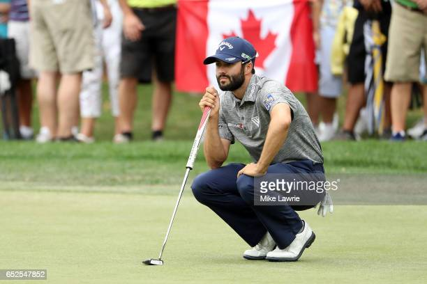 Adam Hadwin of Canada lines up a putt on the second green in front of a Canadian flag during the final round of the Valspar Championship at...