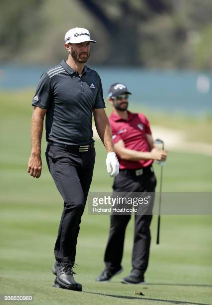 Adam Hadwin of Canada plays a shot on the 14th hole as Dustin Johnson of the United States looks on during the second round of the World Golf...