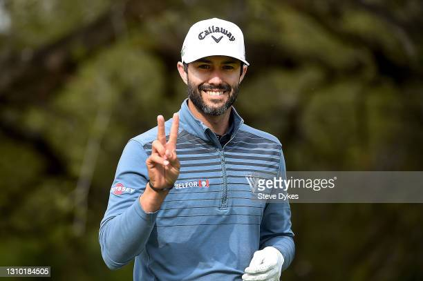 Adam Hadwin of Canada smiles at a photographer as he walks off the tee box on the sixth hole during the pro-am prior to the Valero Texas Open at TPC...