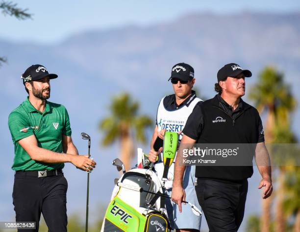 Adam Hadwin of Canada tees off on the 17th hole as Phil Mickelson looks on during the final round of the Desert Classic on the Stadium Course at PGA...