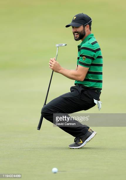 Adam Hadwin of the International Team sinks to his knees as his putt to win his match against Bryson De Chambeau slips by on the 18th hole during the...