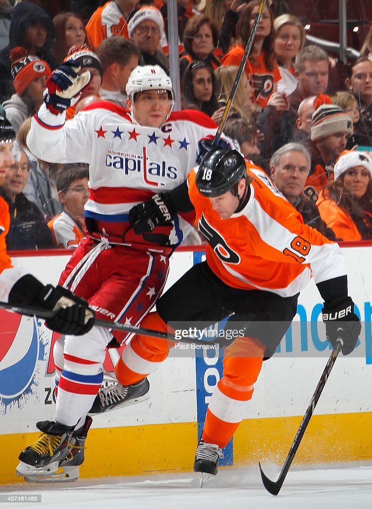 Adam Hall #18 of the Philadelphia Flyers checks Alex Ovechkin #8 of the Washington Capitals during the first period of an NHL hockey game at Wells Fargo Center on December 17, 2013 in Philadelphia, Pennsylvania.
