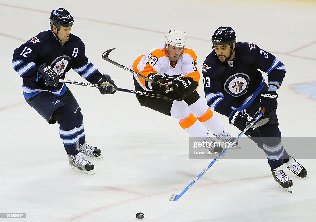 Adam Hall #18 of the Philadelphia Flyers tries to cut between Olli Jokinen #12 and Dustin Byfuglien #33 of the Winnipeg Jets as they chase the loose puck during third period action at the MTS Centre on April 6, 2013 in Winnipeg, Manitoba, Canada.