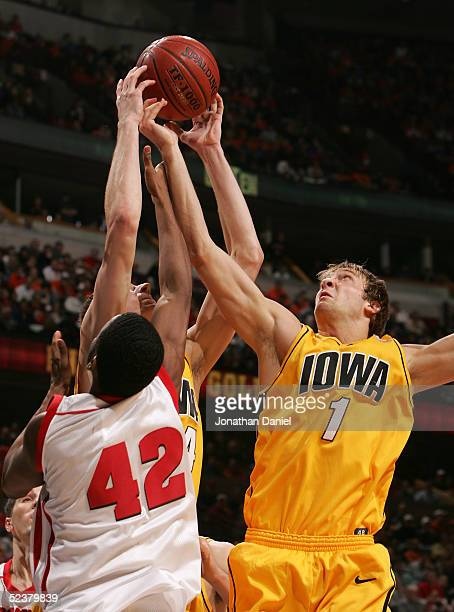 Adam Haluska and Erek Hansen of the Iowa Hawkeyes go up for a rebound against Alando Tucker of the Wisconsin Badgers during the semifinals on the...