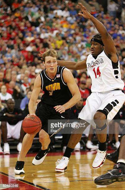 Adam Haluska of the Iowa Hawkeyes drives baseline against Eric Hicks of the Cincinnati Bearcats in the first round game of the NCAA Division I Men's...