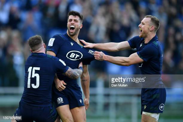 Adam Hastings of Scotland celebrates with Stuart Hogg and Rory Hutchinson after scoring his team's third try during the 2020 Guinness Six Nations...