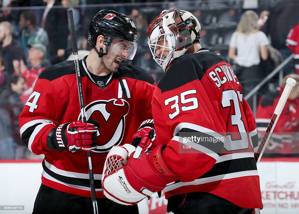 Adam Henrique #14 and Cory Schneider #35 of the New Jersey Devils celebrate the 3-2 win over the Vancouver Canucks on December 6, 2016 at Prudential Center in Newark, New Jersey.