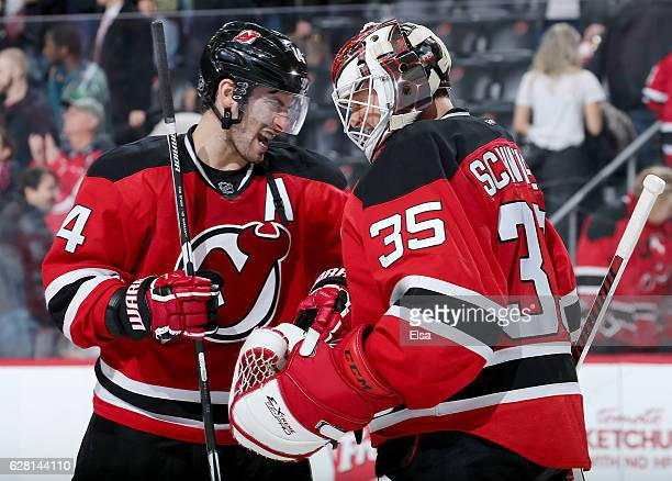 Adam Henrique and Cory Schneider of the New Jersey Devils celebrate the 32 win over the Vancouver Canucks on December 6 2016 at Prudential Center in...