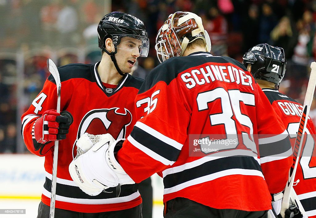 Adam Henrique #14 and Cory Schneider #35 of the New Jersey Devils in action against the Buffalo Sabres at the Prudential Center on February 17, 2015 in Newark, New Jersey. The Devils defeated the Sabres 2-1 after a shootout.