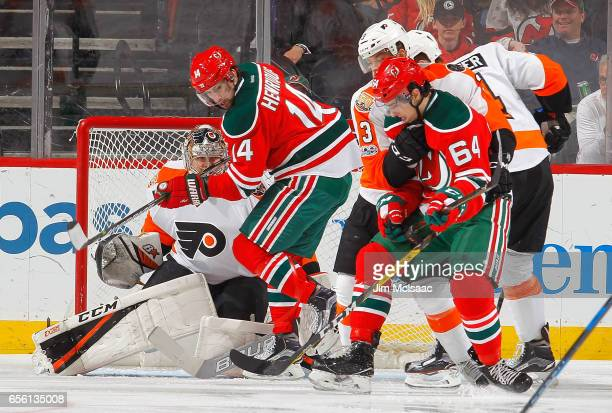 Adam Henrique and Joseph Blandisi of the New Jersey Devils in action against Steve Mason of the Philadelphia Flyers on March 16 2017 at Prudential...