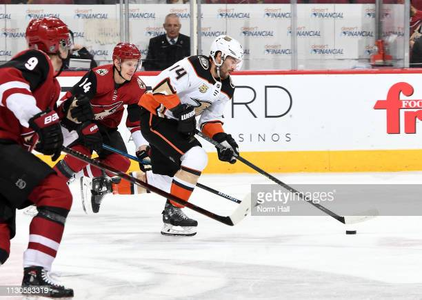 Adam Henrique of the Anaheim Ducks advances the puck up ice ahead of Richard Panik and Clayton Keller of the Arizona Coyotes during the first period...