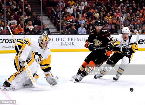 Adam Henrique of the Anaheim Ducks and Patric Hornqvist of the Pittsburgh Penguins chase after a rebound in front of Tristan Jarry of the Pittsburgh...
