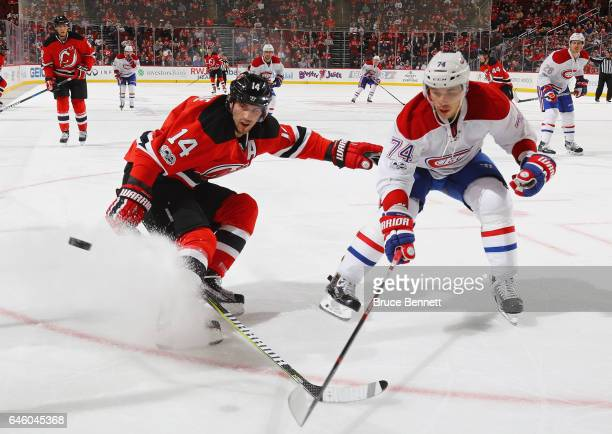 Adam Henrique of the New Jersey Devils and Alexei Emelin of the Montreal Canadiens pursue the puck during the second period at the Prudential Center...