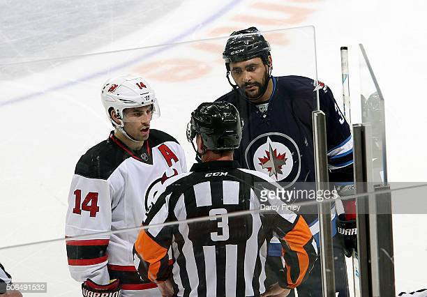 Adam Henrique of the New Jersey Devils and Dustin Byfuglien of the Winnipeg Jets chat with referee Mike Leggo during a second period stoppage in play...