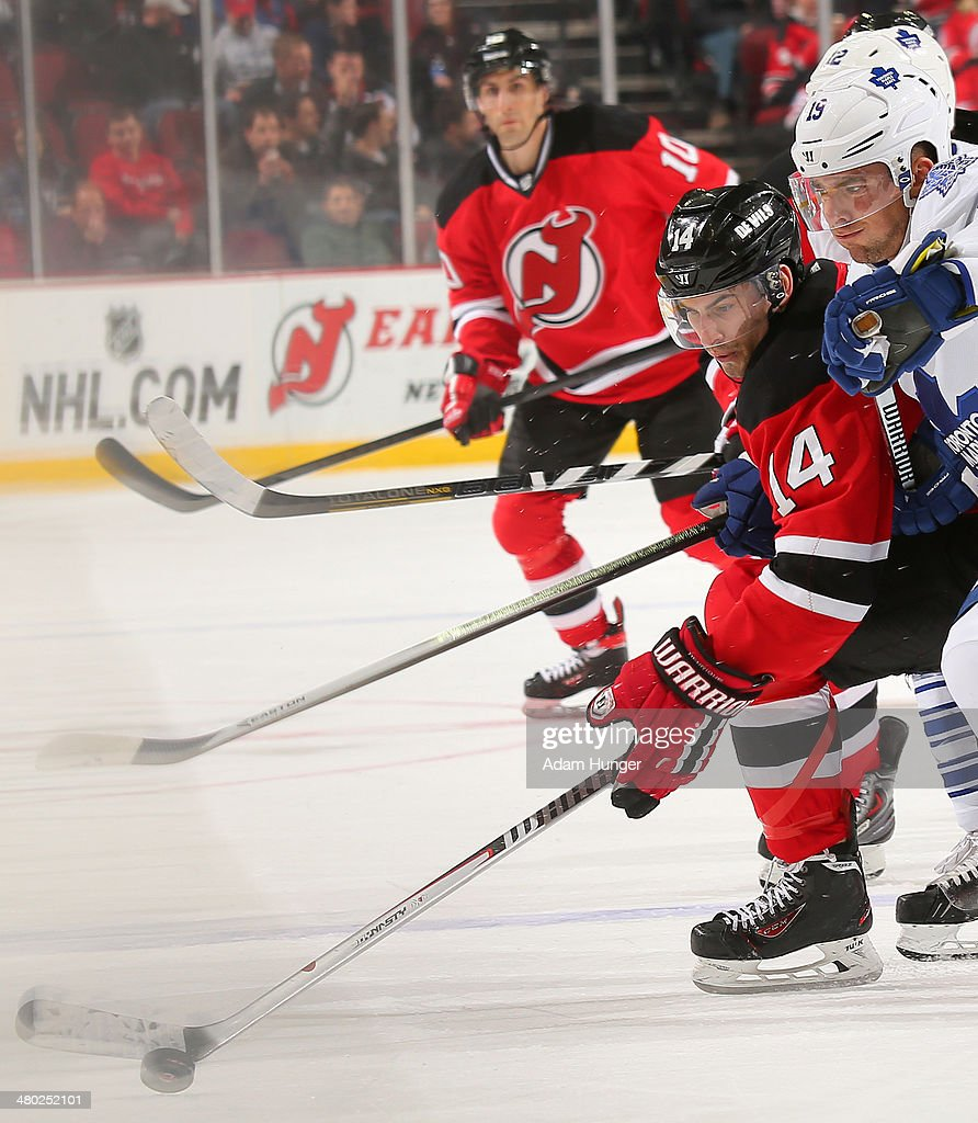 Adam Henrique #14 of the New Jersey Devils and Joffrey Lupul #19 of the Toronto Maple Leafs battle for the puck during the third period at the Prudential Center on March 23, 2014 in Newark, New Jersey. The New Jersey Devils defeated the Toronto Maple Leafs 3-2.