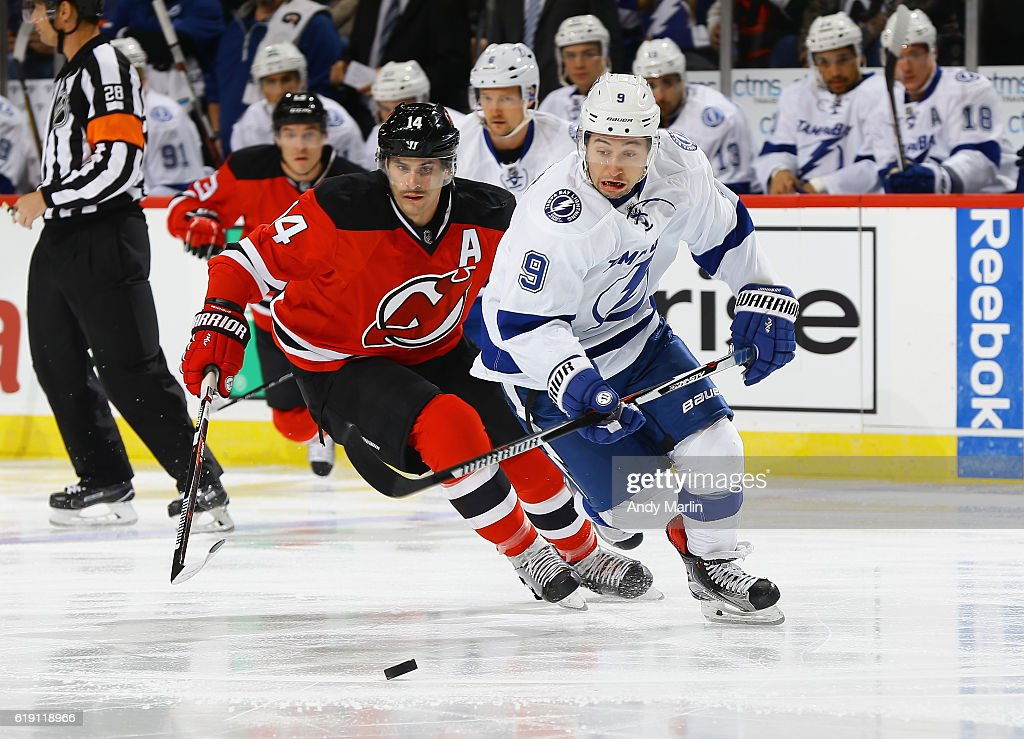 Adam Henrique #14 of the New Jersey Devils and Tyler Johnson #9 of the Tampa Bay Lightning skate towards a loose puck during the game at Prudential Center on October 29, 2016 in Newark, New Jersey.
