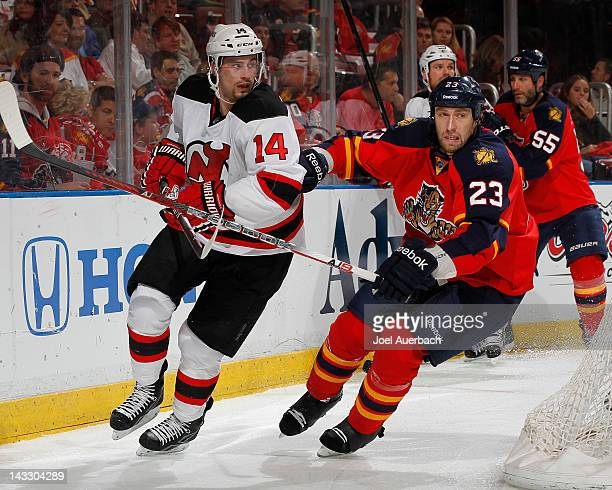 Adam Henrique of the New Jersey Devils and Tyson Strachan of the Florida Panthers chase a loose puck in Game Five of the Eastern Conference...