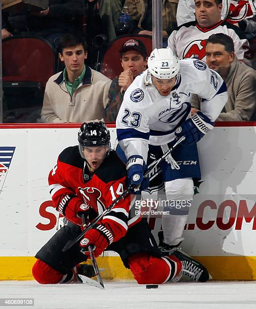 Adam Henrique of the New Jersey Devils attempts to control the puck while battling with JT Brown of the Tampa Bay Lightning at the Prudential Center...