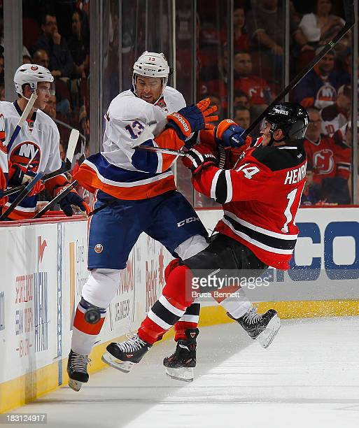 Adam Henrique of the New Jersey Devils bounces off Colin McDonald of the New York Islanders at the Prudential Center on October 4 2013 in Newark New...