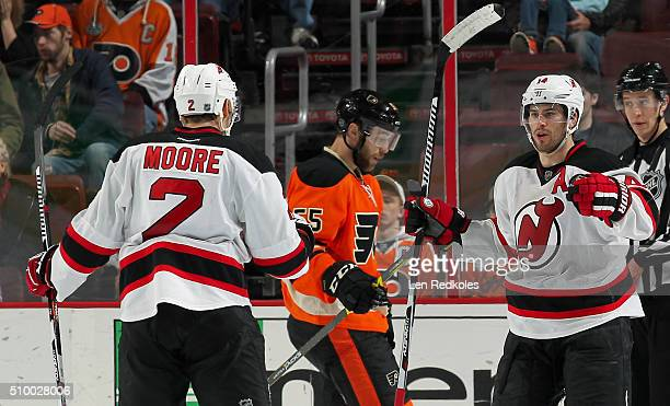 Adam Henrique of the New Jersey Devils celebrates his overtime gamewinning goal against the Philadelphia Flyers with teammate John Moore on February...