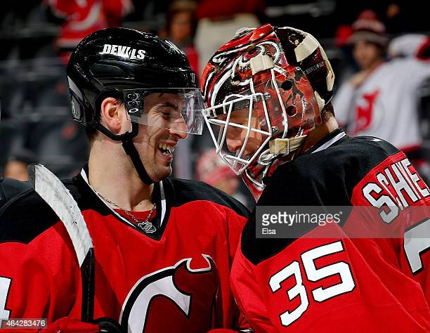 Adam Henrique of the New Jersey Devils congratulates Cory Schneider after Schneider shut out the Arizona Coyotes on February 23 2015 at the...