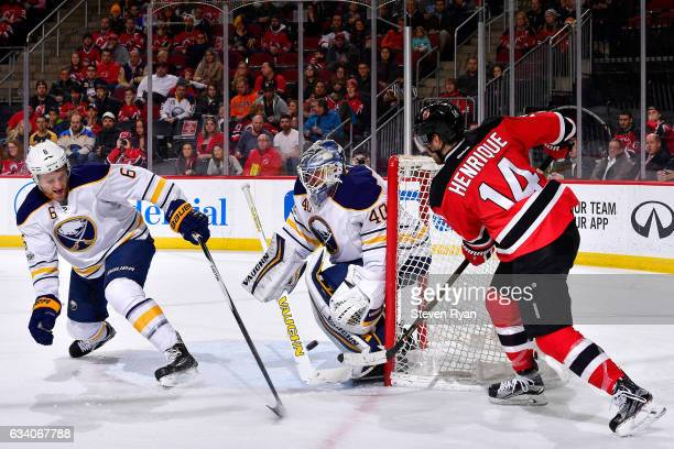 Adam Henrique of the New Jersey Devils deflects the puck off of Cody Franson of the Buffalo Sabres for a second period goal past Robin Lehner at...