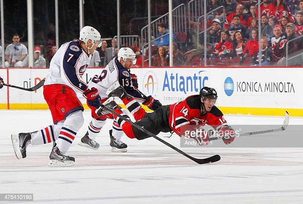 Adam Henrique of the New Jersey Devils falls to the ice after being checked by Jack Johnson of the Columbus Blue Jackets during the game at the...