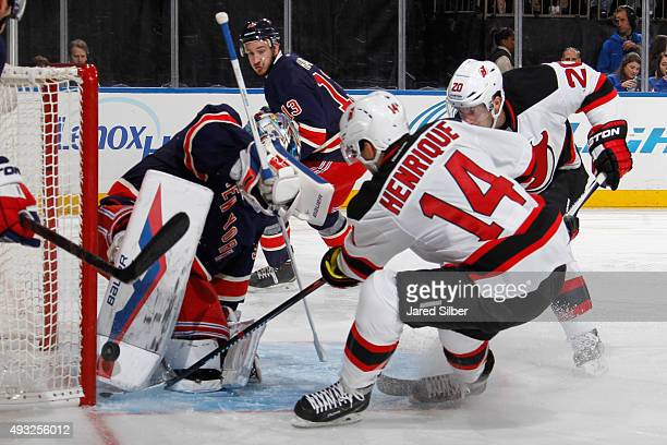 Adam Henrique of the New Jersey Devils jams the puck past Henrik Lundqvist of the New York Rangers for a goal in the second period at Madison Square...