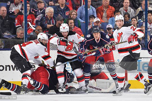 Adam Henrique of the New Jersey Devils knocks Ryan Murray of the Columbus Blue Jackets to the ice as Tyler Kennedy of the New Jersey Devils and...