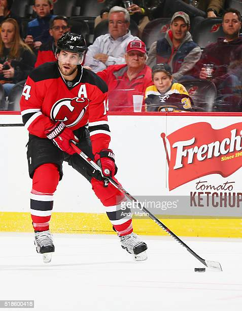 Adam Henrique of the New Jersey Devils plays the puck during the game against the Boston Bruins at the Prudential Center on March 29 2016 in Newark...