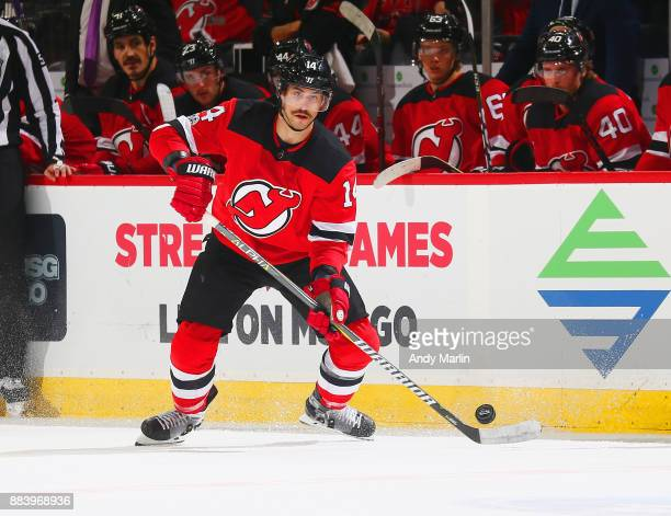 Adam Henrique of the New Jersey Devils plays the puck during the game against the Florida Panthers at Prudential Center on November 27 2017 in Newark...