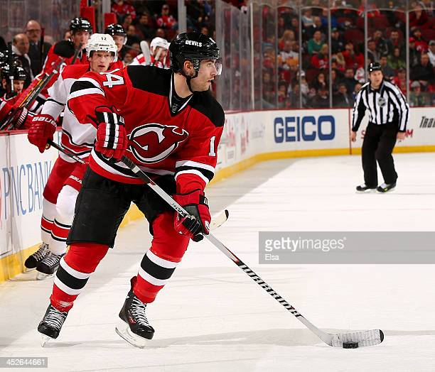 Adam Henrique of the New Jersey Devils takes the puck in the second period against the Carolina Hurricanes at Prudential Center on November 27 2013...