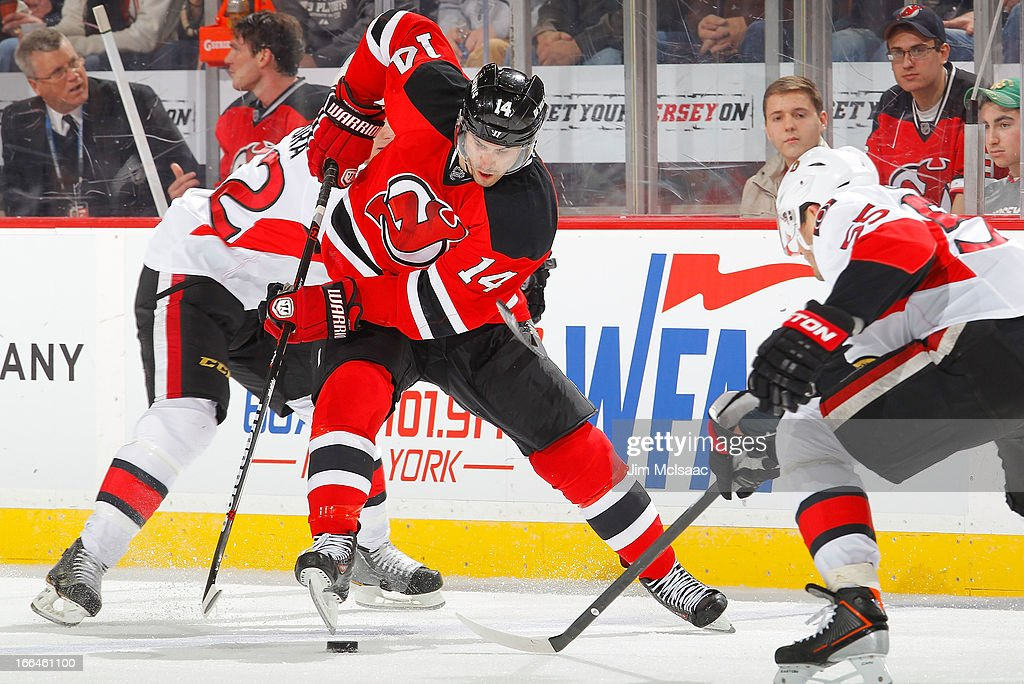 Adam Henrique #14 of the New Jersey Devils tries to control the puck against the Ottawa Senators at the Prudential Center on April 12, 2013 in Newark, New Jersey.