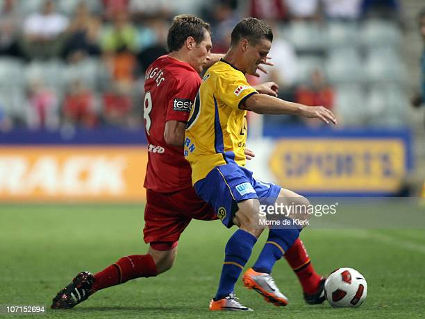 Adam Hughes of Adelaide and Jason Culina of the Gold Coast competes for the ball during the round 16 ALeague match between Adelaide United and Gold...